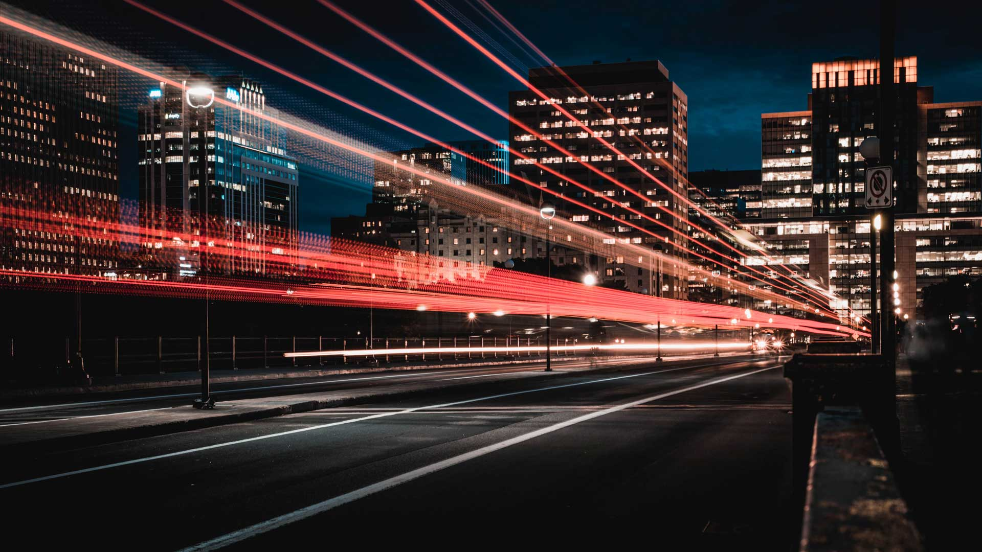 Long exposure of a city street at night with white headlight trails and red taillight trails